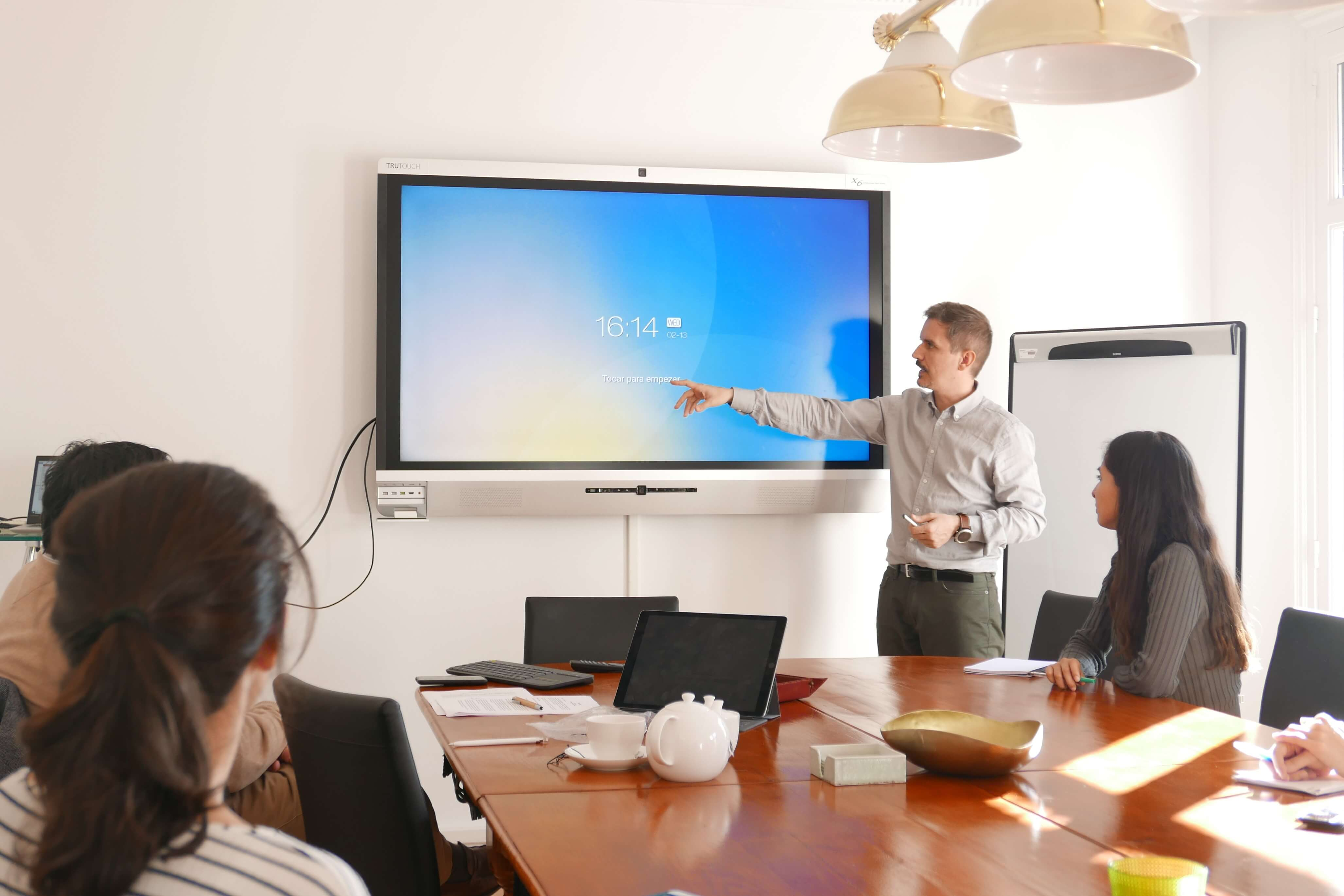 person speaking in meeting on interactive display