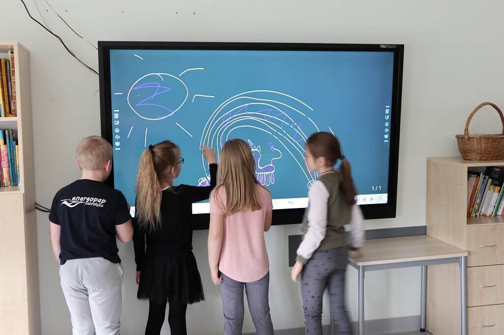 Multiple students interacting on whiteboard in classroom