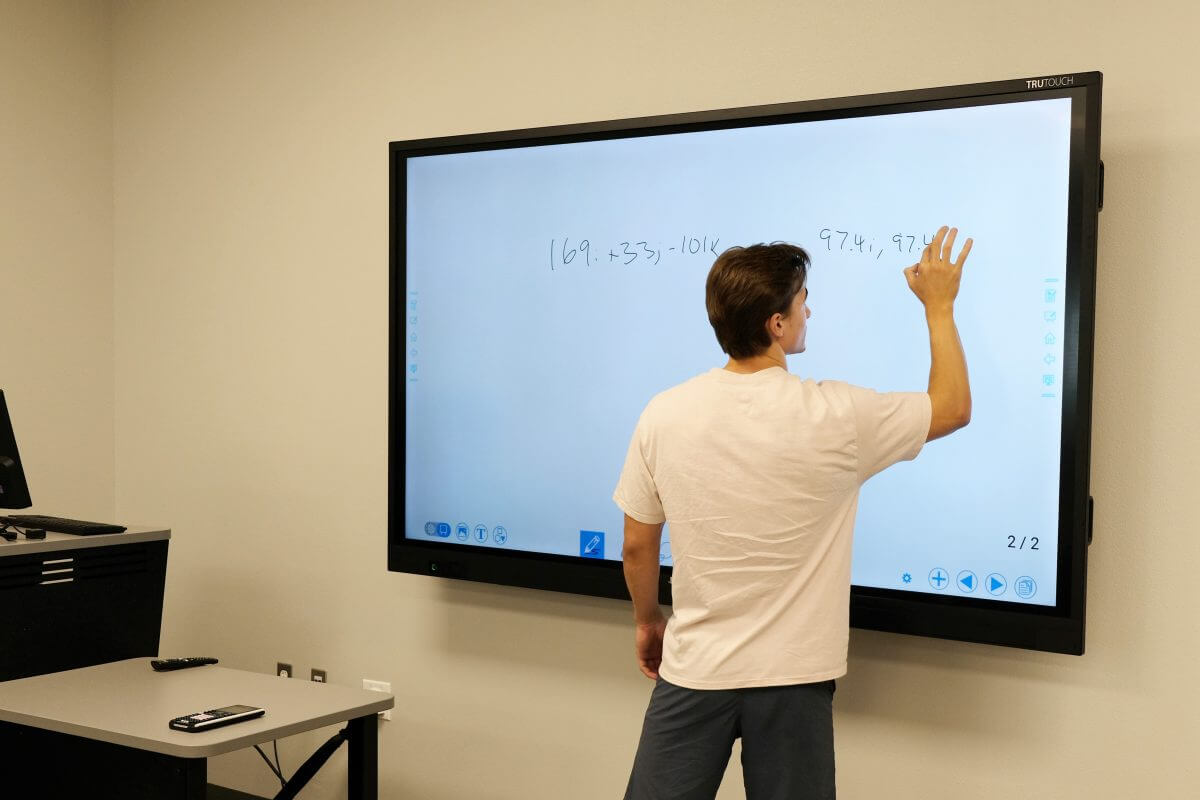 teacher writing on the interactive display in class