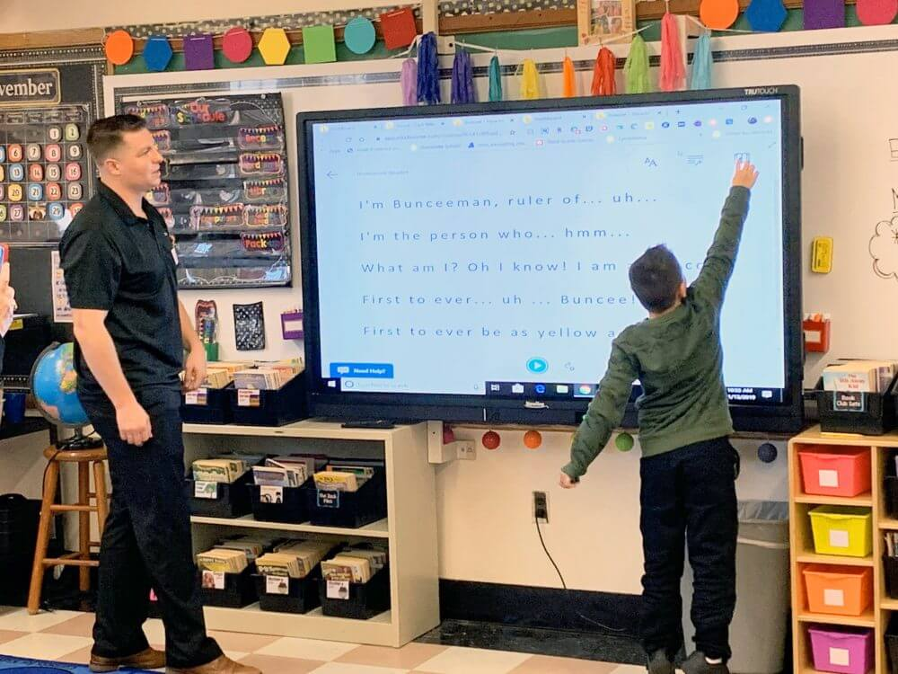 student touch interactive display in front of classroom
