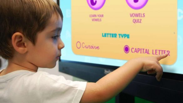 young student touching interactive display