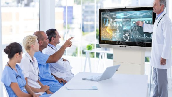 people collaborating on interactive display during healthcare meeting